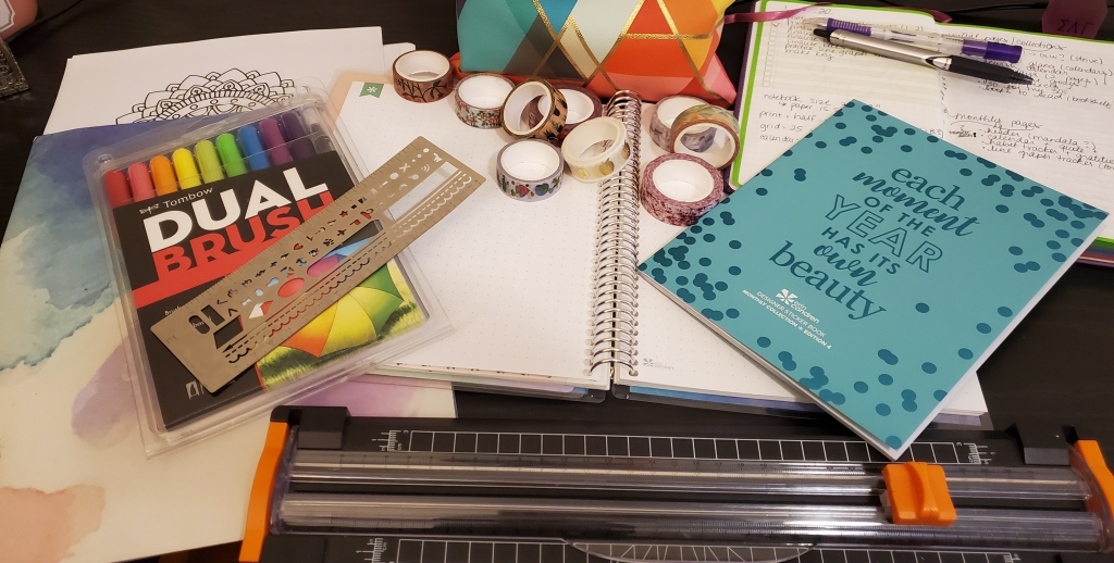 a variety of bullet journal supplies including stickers, a paper cutter, a ruler, washi tape, brush pens, and a notebook.