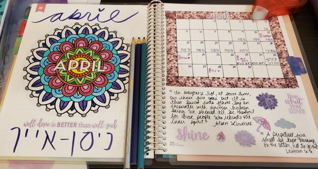 "photograph of an open notebook. on the left page, a mandala header that says ""April."" on the right page, the April calendar, framed with washi tape and decorated decorated with quotes and stickers."